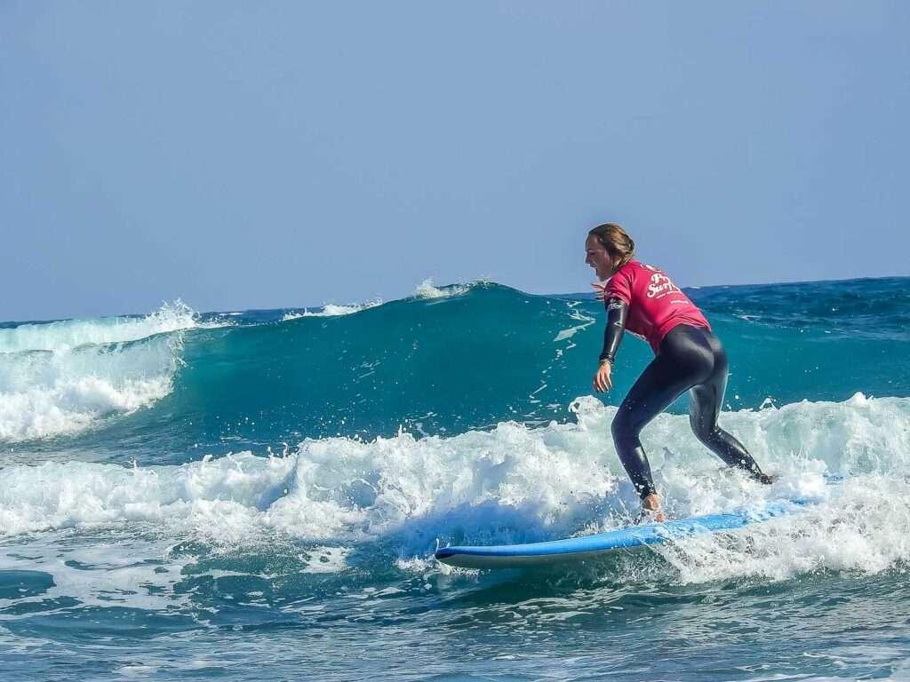 Joven alumna de Prosurfing, disfrutando de la práctica del surf en la playa de Maspalomas en Gran canaria. España